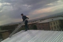 The rescuers dismantled an iron sheet-lead hanging from the roof of a building